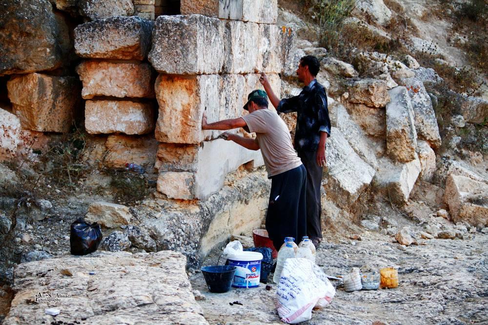عصام يقوم بإزالة الكتابات على الأثار رفقة أحد زملائه | تصوير : علي الساعدي