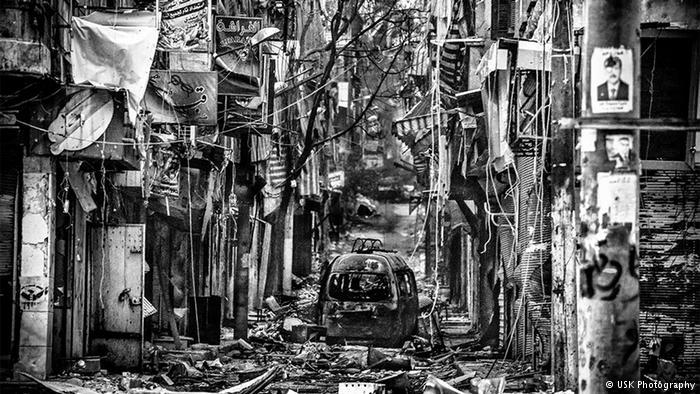 """سافر يوسوكي سوزوكي 2013 عبر الحدود التركية إلى حلب السورية. هذه الصورة تكشف ضمن سلسلة صوره """"مدينة الفوضى"""" شارعا للتجول كان يقصده شباب المدينة سابقا. """"عندما وصلت إلى حلب اتضح لي أنه لا وجود للماء وللغاز للكهرباء أو حتى الأدوية والمدارس والعمل أو حليب للأطفال""""."""
